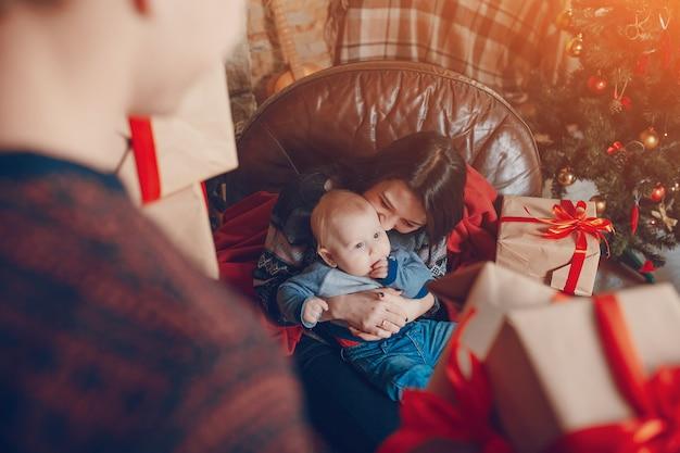 Femme assise sur un canapé avec un bébé dans ses bras et avec une montagne de cadeaux marron avec noeud rouge