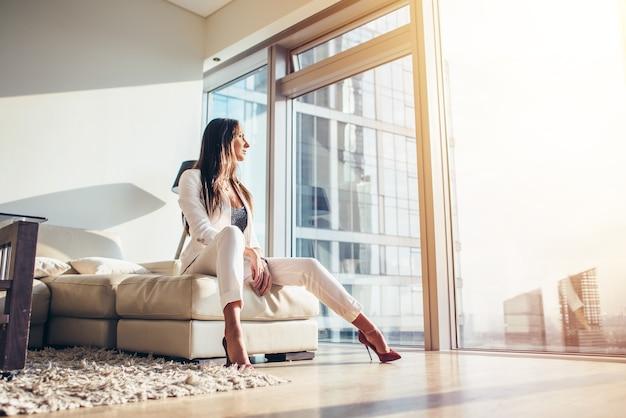 Femme assise sur un canapé dans un appartement moderne.