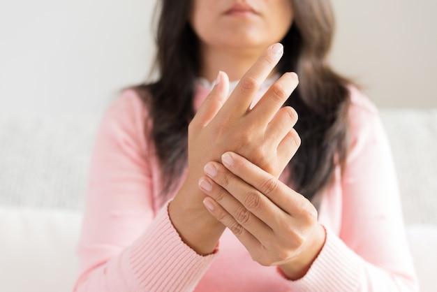 Une femme assise sur un canapé lui blesse la main, ressentant de la douleur.