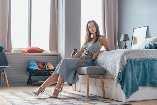 Femme assise sur un canapé à la maison en regardant la caméra