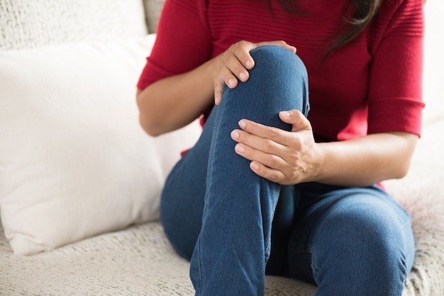 Femme assise sur le canapé et le sentiment de douleur au genou, soins de santé et concept médical.