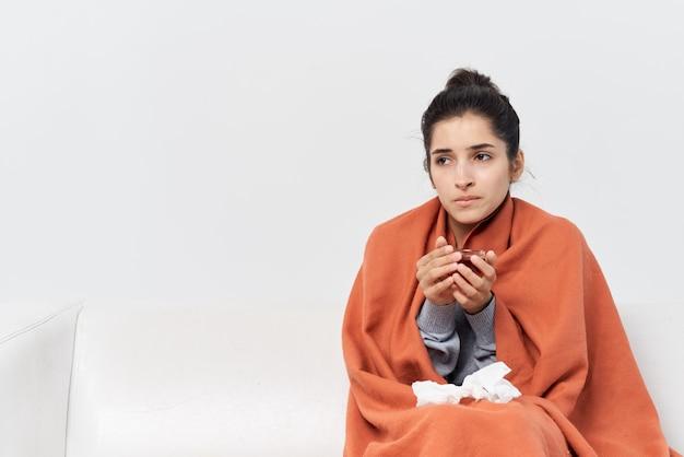 Femme assise sur le canapé avec une tasse de thé et traitant une insatisfaction froide
