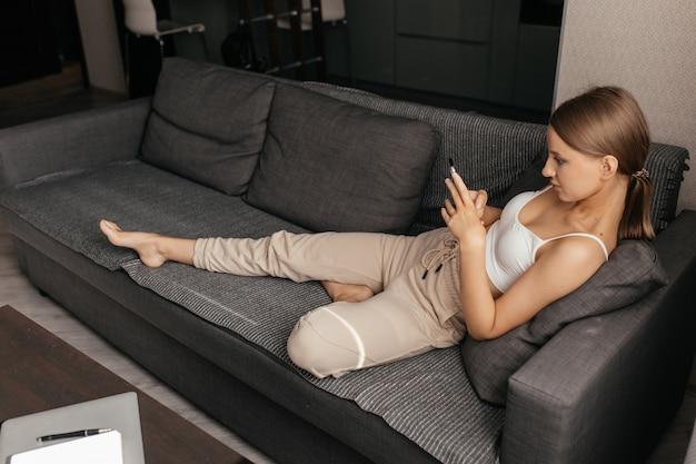 Une femme assise sur le canapé avec un téléphone