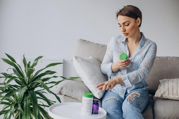 Femme assise sur un canapé et tenant des pilules vitamines