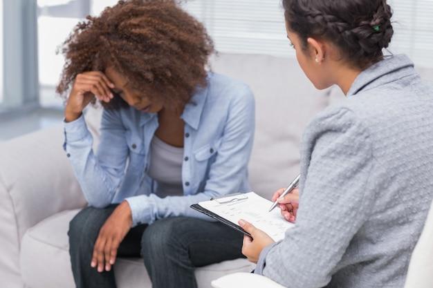Femme assise sur le canapé de thérapeutes en regardant vers le bas