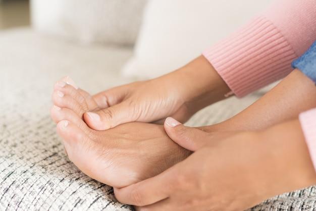 Femme assise sur un canapé tient sa blessure au pied, ressentant la douleur. concept de soins de santé.