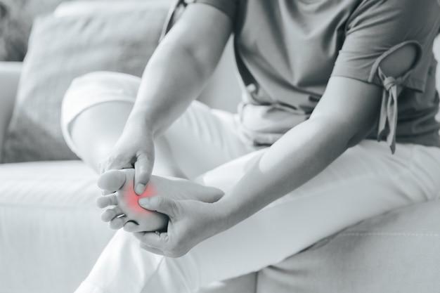 Femme assise sur le canapé et tient son pied souffrant de douleurs au pied avec surbrillance rouge