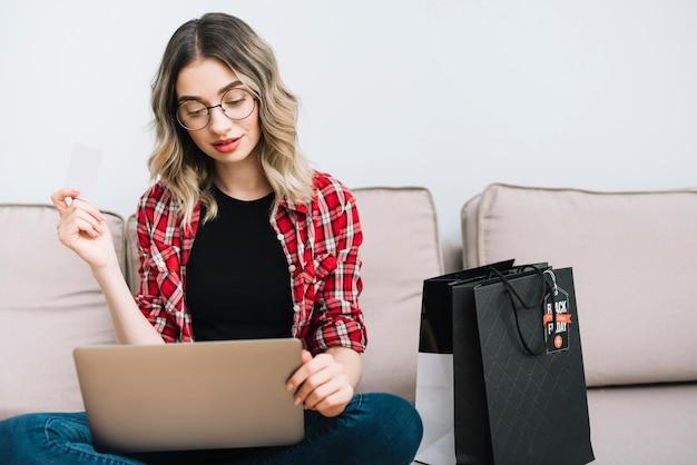 Femme assise sur un canapé en train d'étudier les ventes le vendredi noir