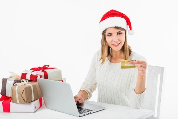 Femme assise avec carte de crédit à table