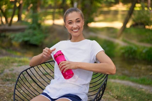 Femme assise chaise boire de l'eau bouteille rouge après l'entraînement du matin