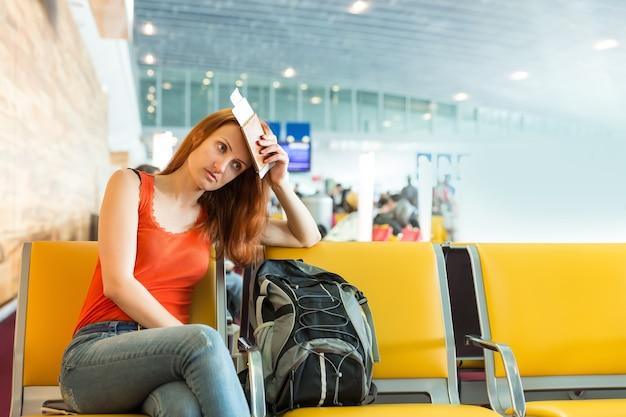 Femme assise sur la chaise dans un hall de la gare.