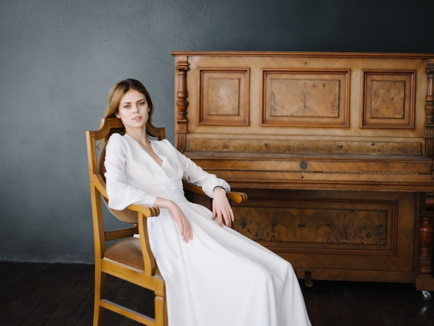 Femme assise sur une chaise près de l'intérieur de l'instrument de musique piano posant