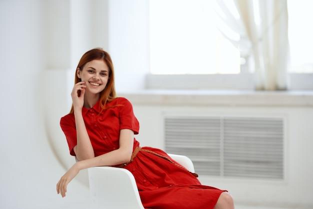 Femme assise sur une chaise robe rouge posant la salle. photo de haute qualité