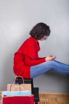Femme assise sur une chaise avec smartphone