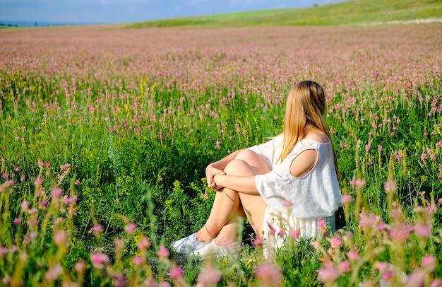 Femme assise sur le champ fleuri de sainfoin. femme, fleurir, champ, rose