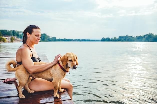 Femme assise avec chien sur le quai
