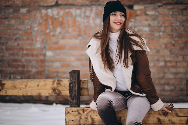 Femme assise sur une clôture à l'extérieur en hiver