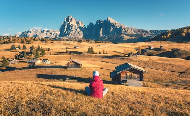 Femme assise sur la colline à la recherche sur les prairies et les montagnes au coucher du soleil en automne