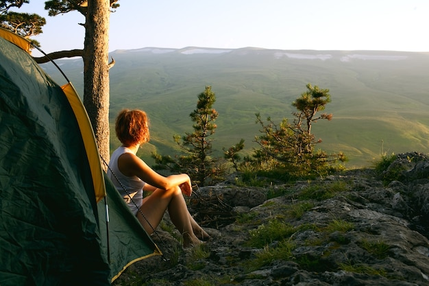 Femme assise à côté de la tente au coucher du soleil