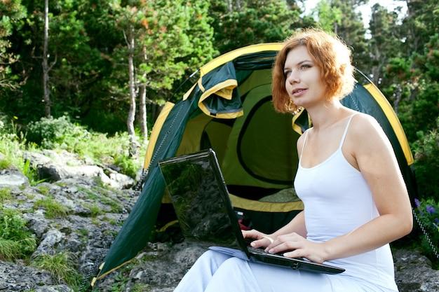 Femme assise à côté d'une tente avec un ordinateur portable