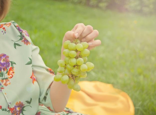 Femme assise sur la couverture jaune et tenant une grappe de raisin.