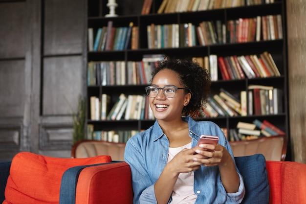 Femme assise dans une bibliothèque avec son téléphone