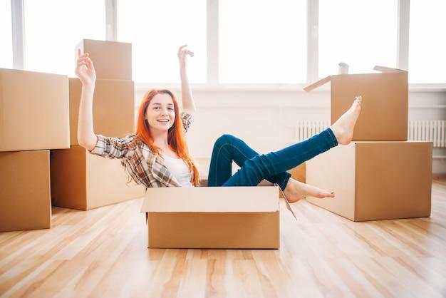Femme assise dans une boîte en carton, pendaison de crémaillère