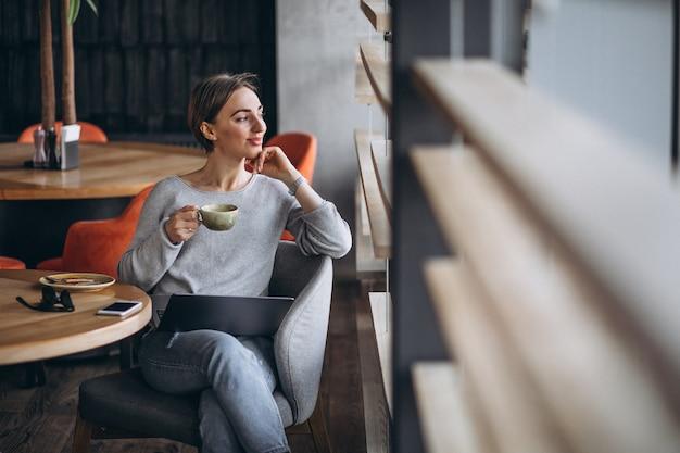 Femme assise dans un café, buvant du café et travaillant sur un ordinateur