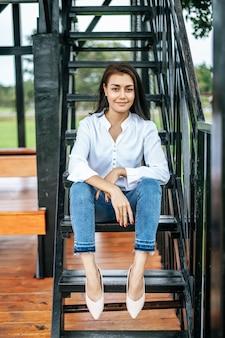 Femme assise dans l'escalier et regardant vers l'avant
