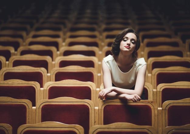 Femme assise dans les fauteuils d'un théâtre