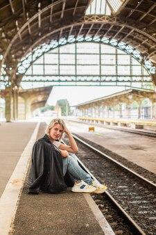 Une femme assise dans une gare rétro