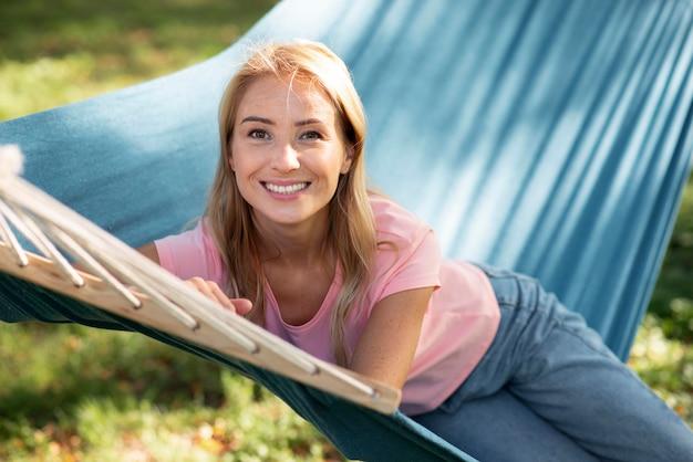 Femme assise dans un hamac à l'extérieur