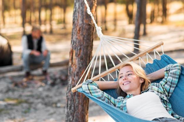 Femme assise dans un hamac homme flou en arrière-plan