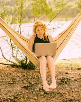 Femme assise dans un hamac avec ordinateur portable