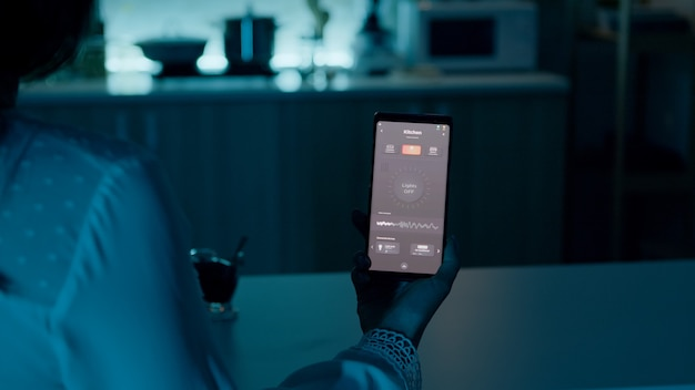 Femme assise dans la maison avec système d'éclairage d'automatisation tenant un smartphone