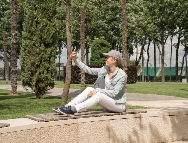 Femme assise dans le parc à l'extérieur prenant selfie sur son téléphone portable