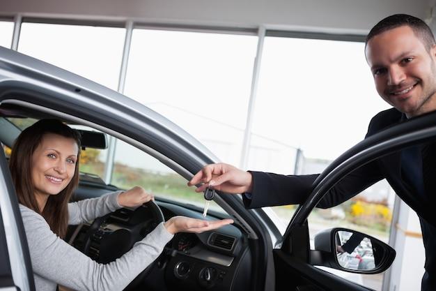 Femme assise dans sa voiture tout en prenant soin de sa main