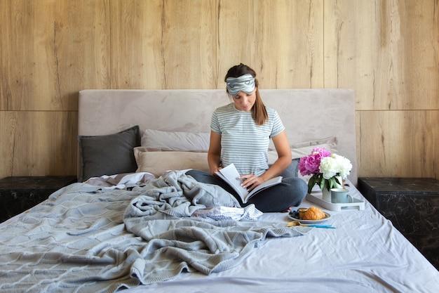 Femme assise dans son lit en lisant un livre et prenant son petit déjeuner.