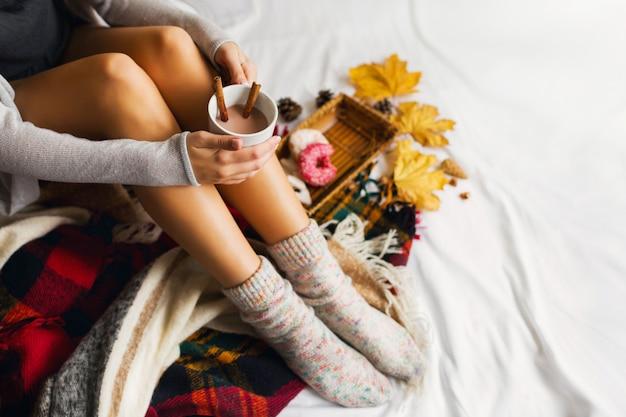 Femme assise dans son lit avec des livres et boire du café avec de la cannelle, des biscuits et des beignets glacés.