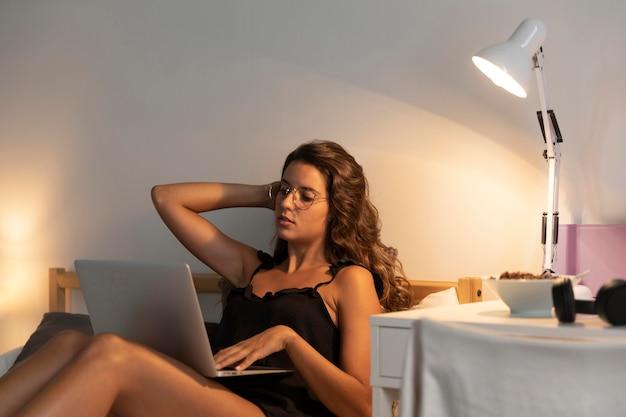 Femme assise dans son lit avec ordinateur portable