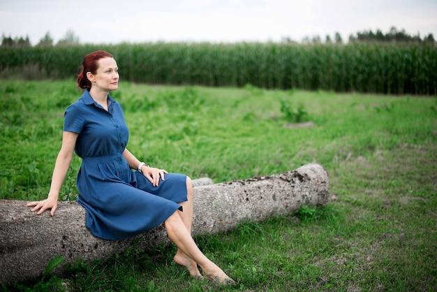 Femme assise dans un tronc d'arbre dans le champ