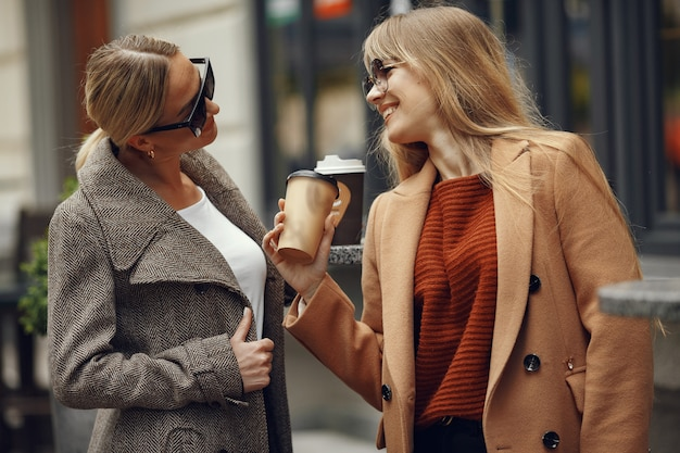 Femme assise dans une ville d'été et boire du café