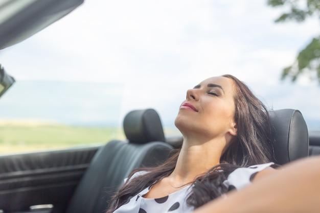 Femme assise dans une voiture cabrio souriante, les yeux fermés, se reposer et faire la sieste.