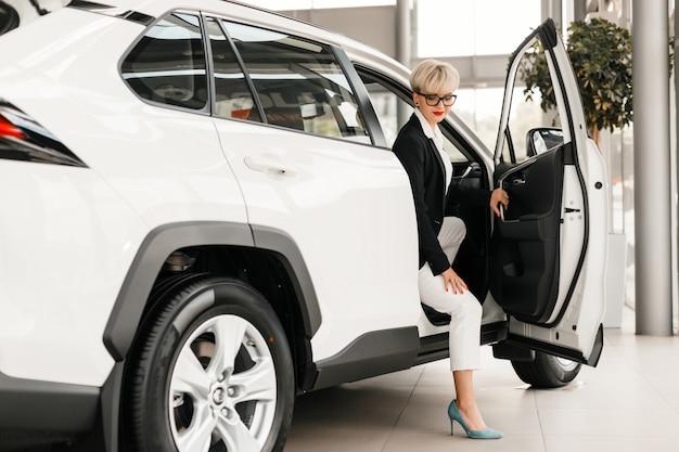 Femme assise dans une voiture chez un concessionnaire.