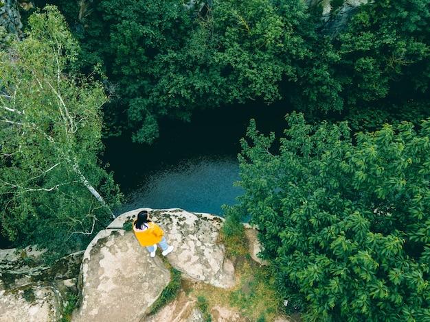 Femme assise sur le dessus, profitant de la vue sur la forêt de la rivière canyon