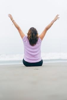 Femme assise sur le dos dans le sable avec ses bras levés formant le v pour la victoire et le triomphe.