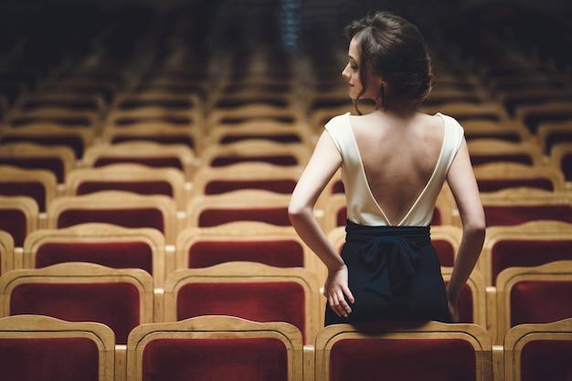 Femme assise sur le dos de quelques places de théâtre