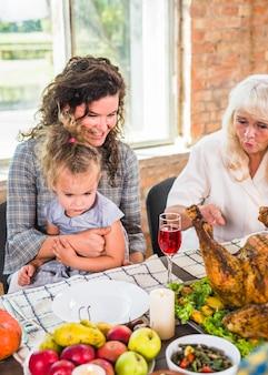 Femme assise avec un enfant à la table près d'une dame âgée
