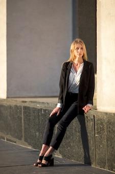 Femme assise sur une fondation de bâtiment
