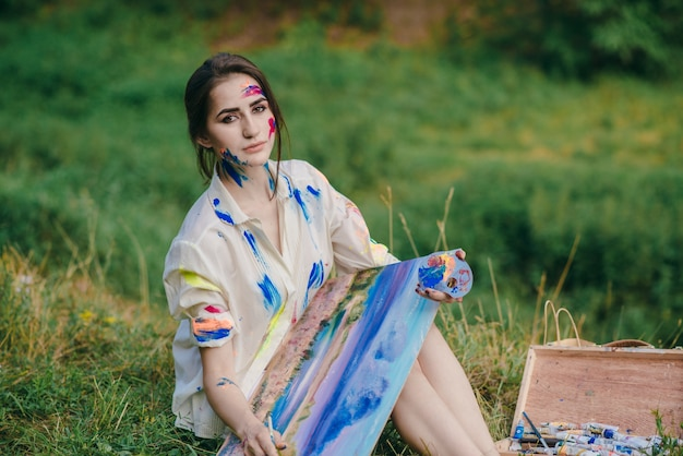 Femme assise sur l'herbe dans une forêt avec une image sur ses jambes